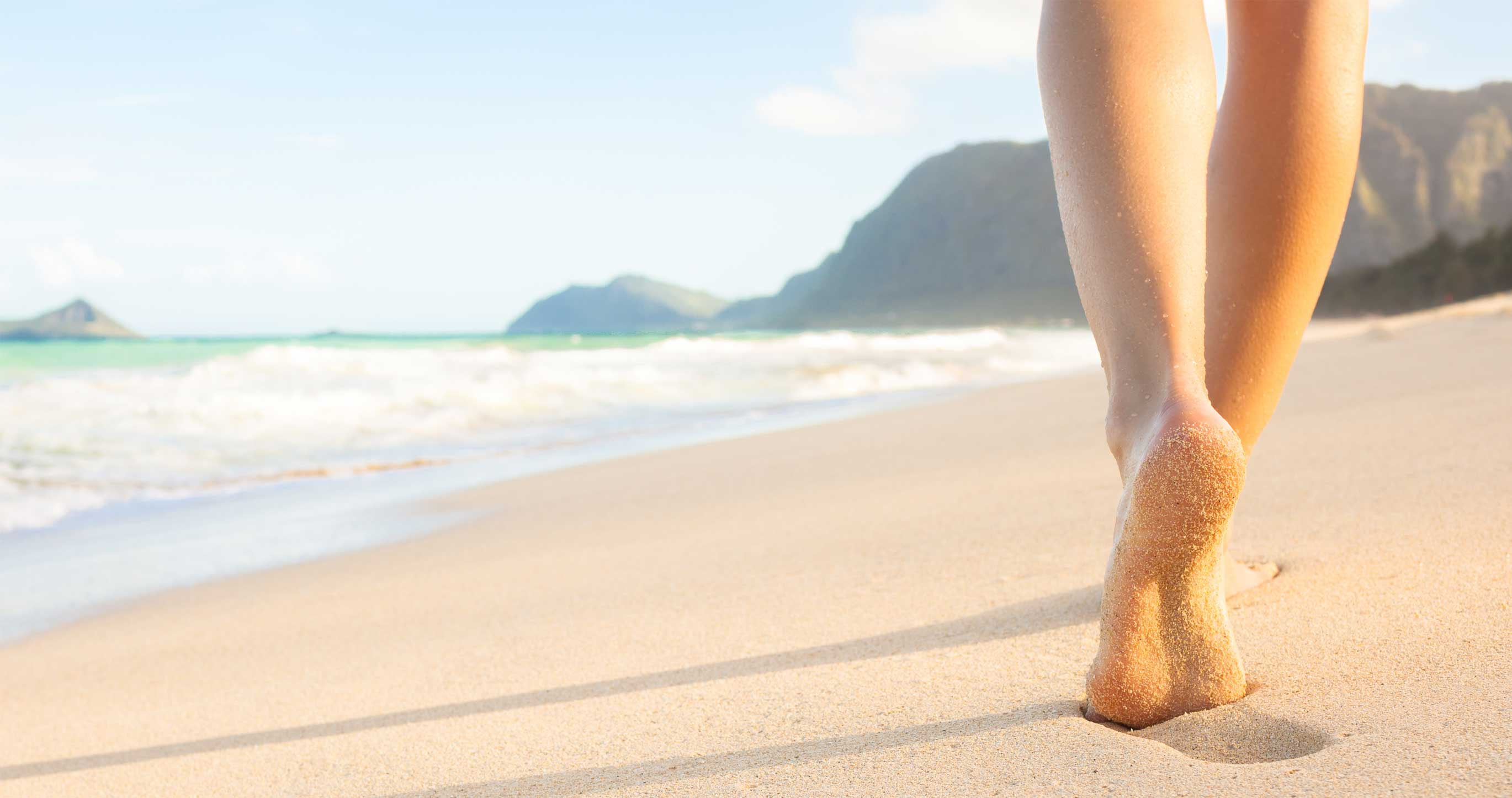 woman walks on beach pain free